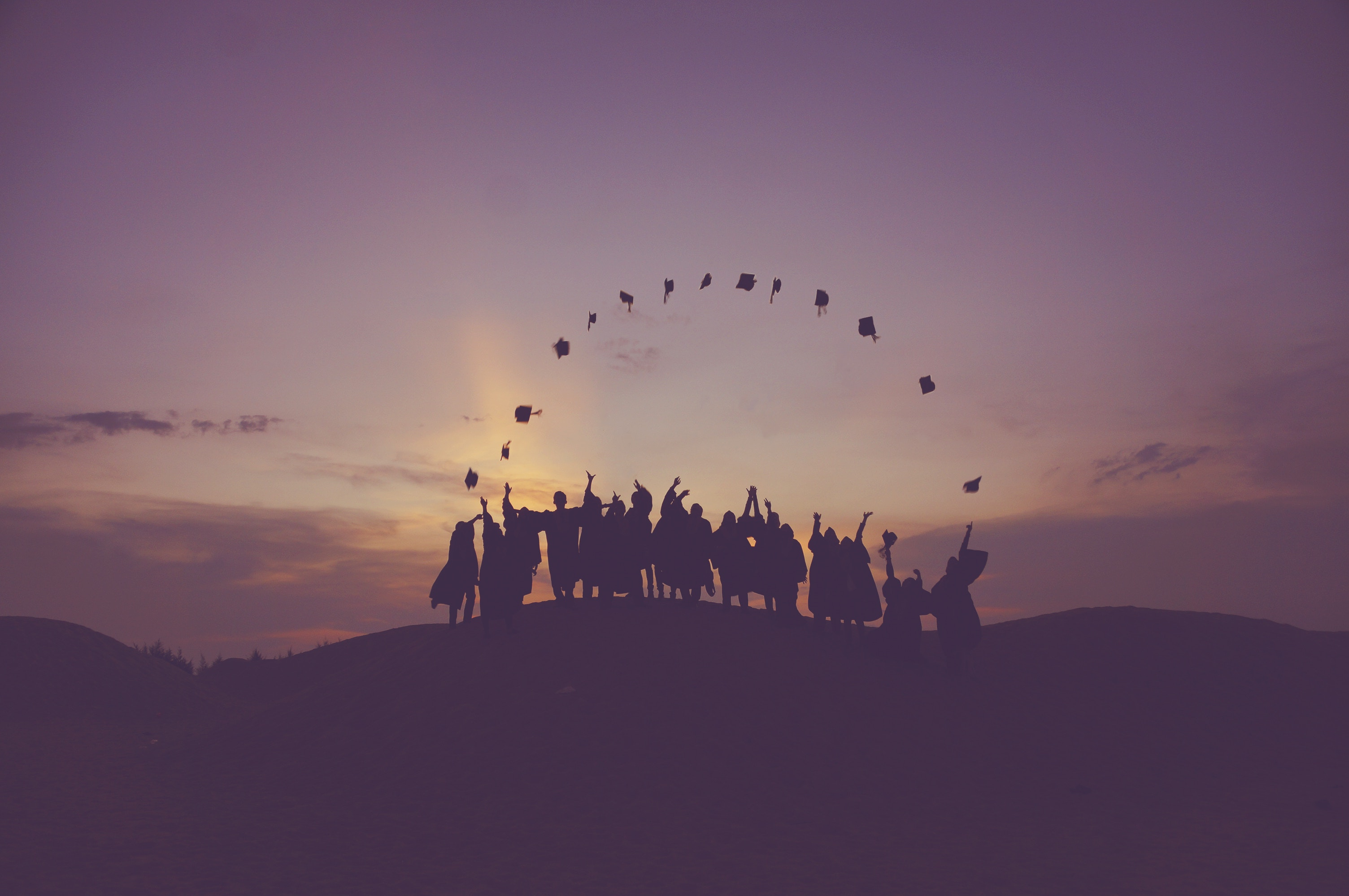 A silhouette of several people on a hill at sunset throwing their graduation caps into the sky.