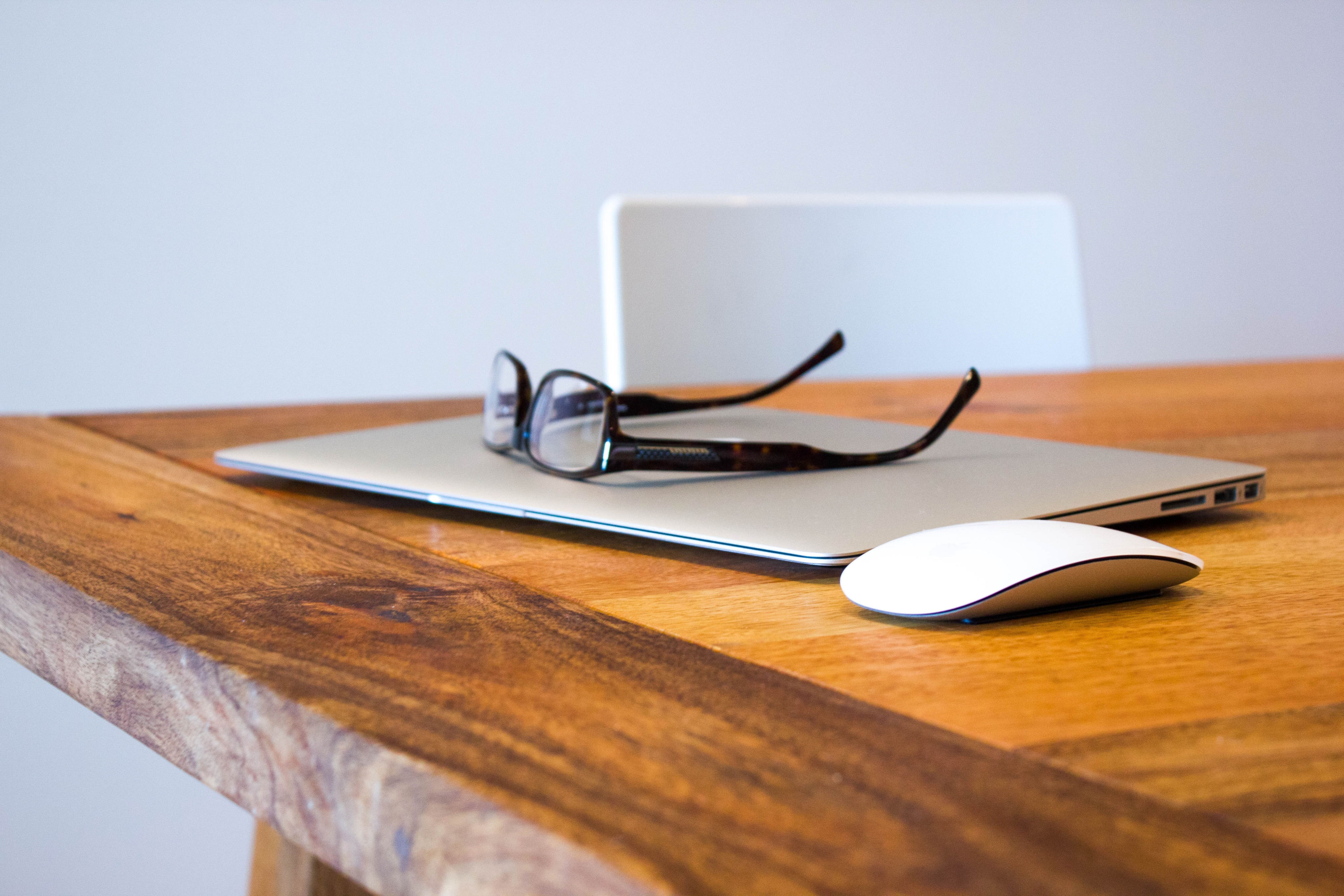 A pair of glasses on top of a laptop, next to a mouse on a wooden table.