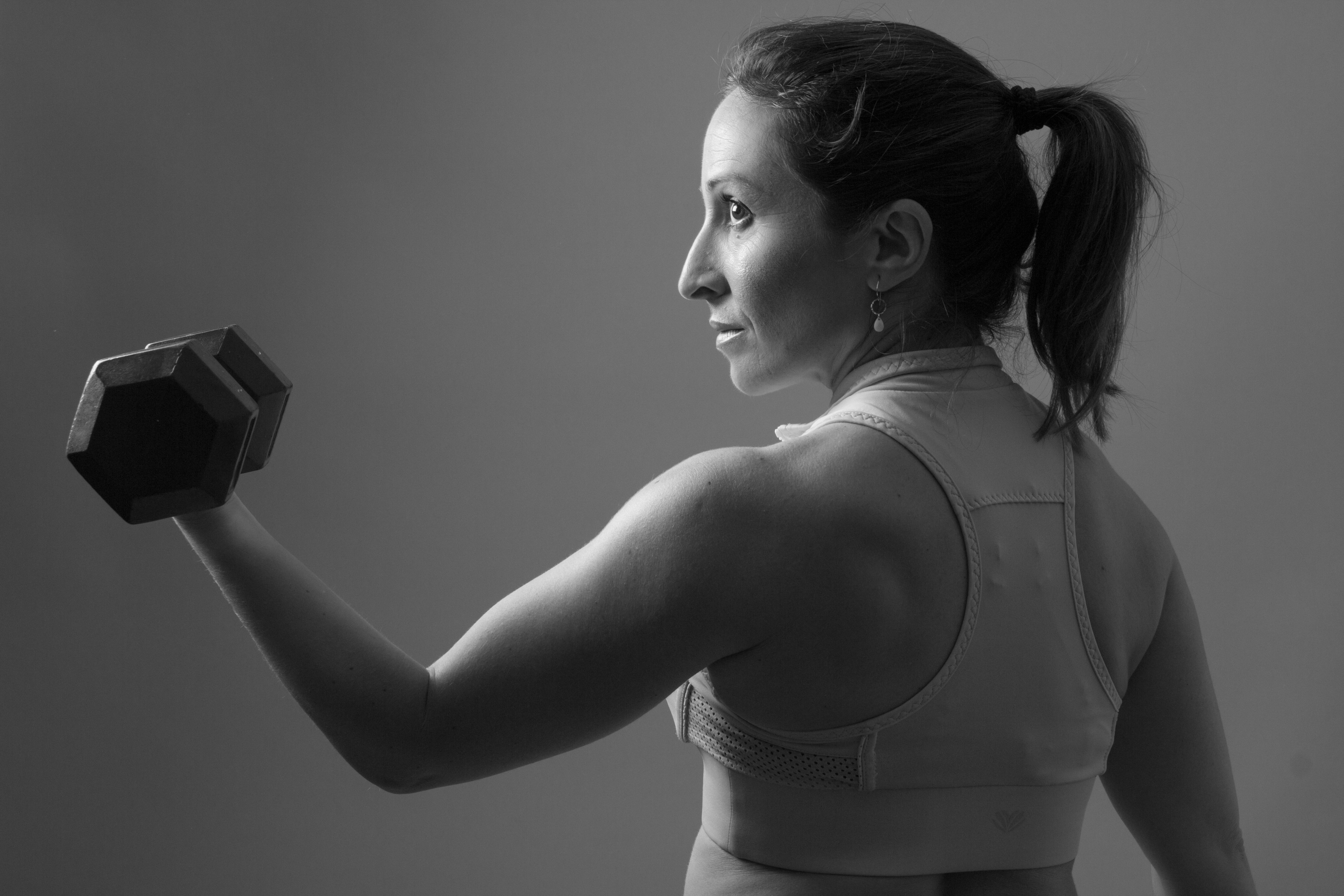 A black and white image of a woman curling a dumbbell.