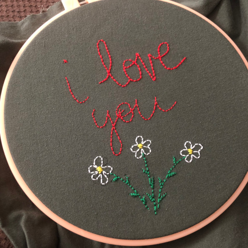 """My second embroidery piece ever that reads """"I love you"""" in red cursive and has three white flowers below the words."""