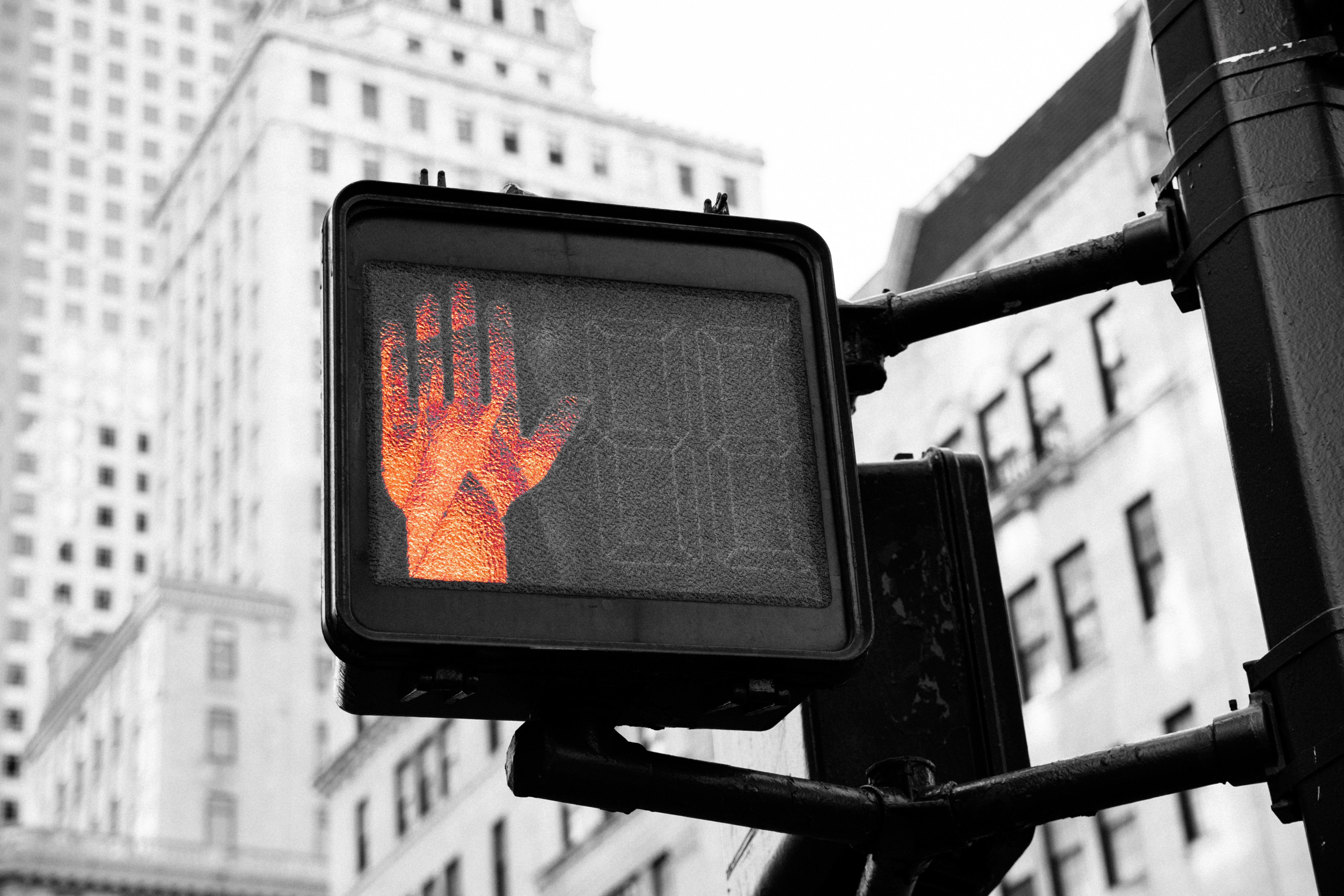 "Close-up of a cross-walk sign with the orange ""Do not walk"" hand displayed."